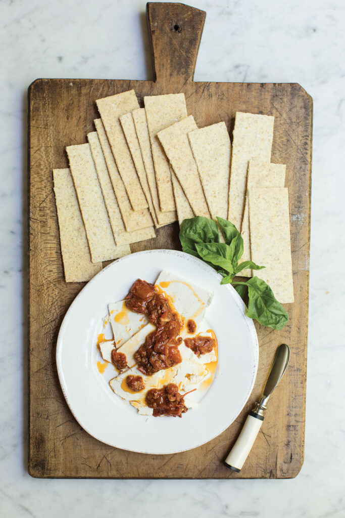 Plate of marinated cheese on a wooden cutting board