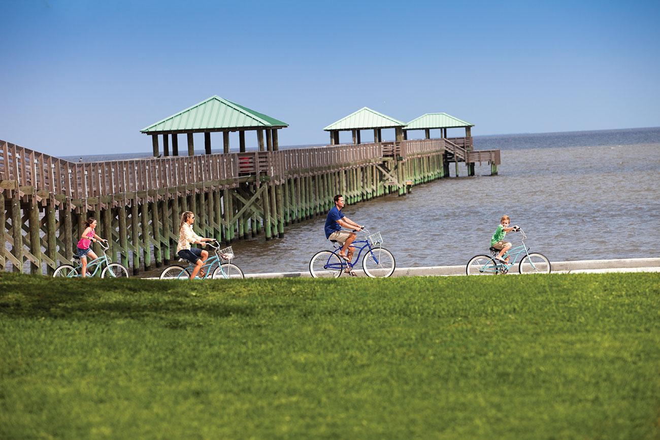 Family biking along the beach in Ocean Springs
