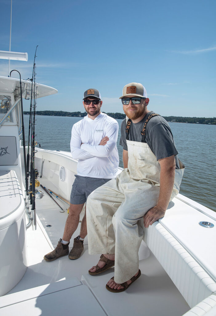 Fairhope Fish House founders sitting on a boat