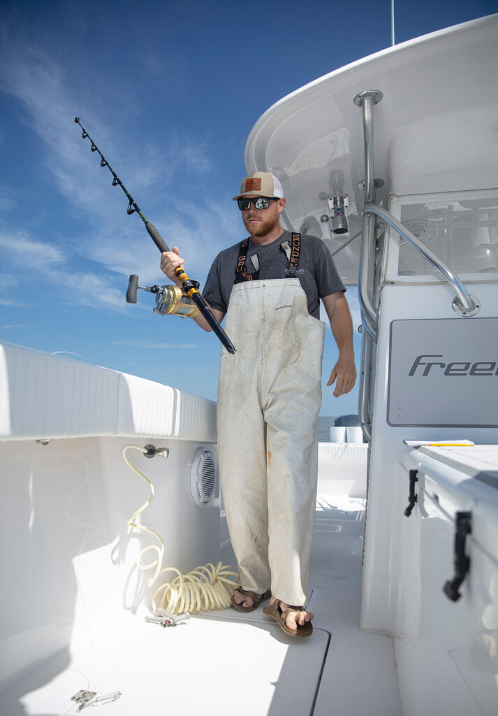 Man holding a fishing pole on a boat