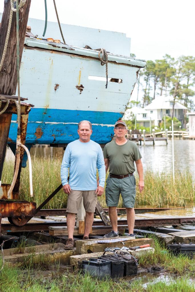 Two men standing in front of a Resmondo boat